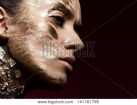 Beautyful girl with gold glitter on her face.Art image beauty face. Picture taken in the studio.