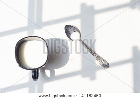 Black Cup Of Milk And Spoon On Natural White Background, Top View