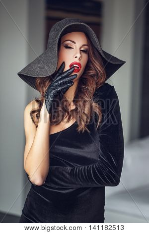 Sensual milf woman with red lips in hat and gloves closed eyes