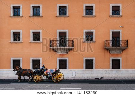 Palma de Mallorca Spain - May 27 2016: Horse-drawn carriage in front of texture of multistorey apartment house wall with balconies and windows in the resort of Palma de Mallorca