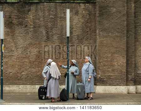 ROME ITALY - CIRCA JULY 2016: four unidentified nuns waiting for the bus at the bus station