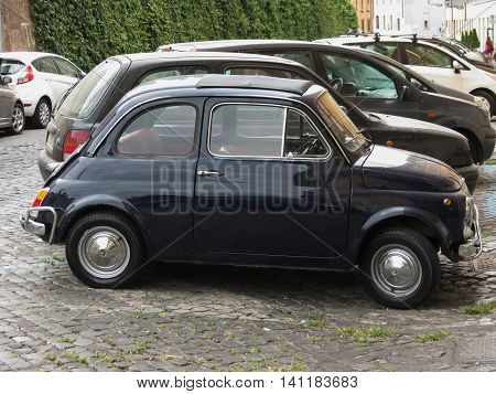 ROME ITALY - CIRCA JULY 2016: black Fiat 500 car in a street of the city centre