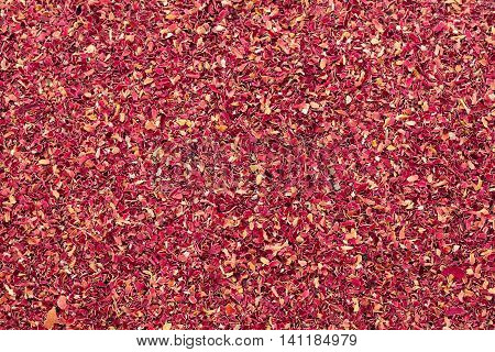 Organic dry Damask rose petals (Rosa damascena) in big cut size. Macro close up background texture. Top view.