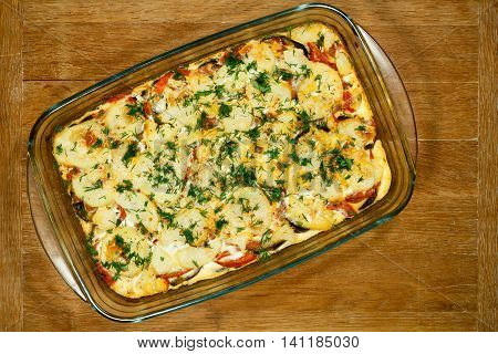 Vegetarian Moussaka. Traditional Greek dishes. Casserole with eggplants. Ingredients: aubergine potatoes tomatoes garlic egg yogurt onions nutmeg oregano. Transparent glass baking dish.