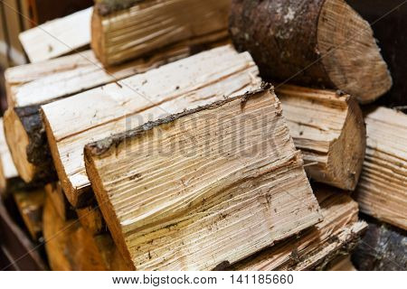 stove heating, fuel and wood concept - close up of firewood pile