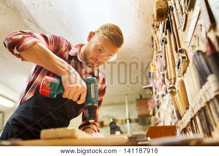 profession, people, carpentry, woodwork and people concept - carpenter with electric drill drilling wood plank at workshop