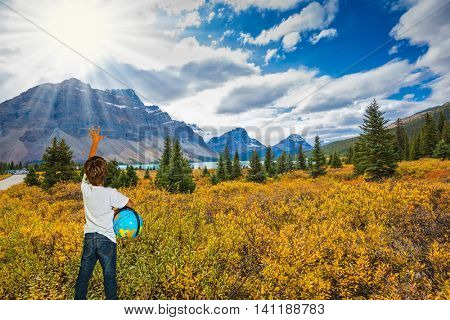 Bow Lake -  glacial lake in the Banff National Park in the Canadian Rockies. The seven-year boy with the globe in hands admire nature