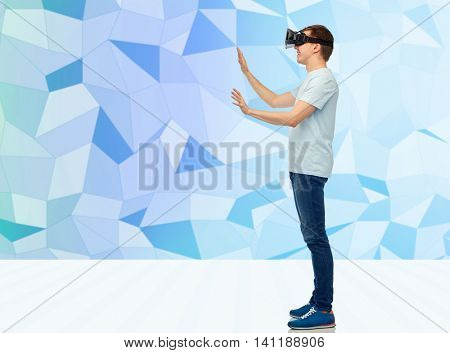 3d technology, virtual reality, entertainment, cyberspace and people concept - happy young man with virtual reality headset or 3d glasses playing game and touching something over low poly background