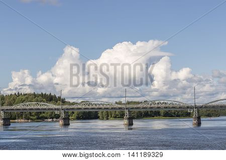 Bridge over River in Umea Sweden with a partly cloudy sky.