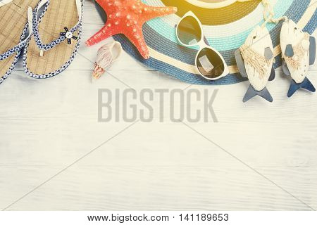 Beach accessories. Flip flops, hat and starfish on wooden background. Top view with copy space. With sun beam