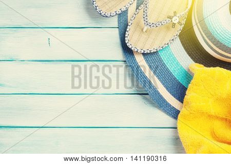 Beach accessories. Flip flops, hat and towel on wooden background. Top view with copy space. With sun beam