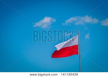 The waving polish national flag of the mast on blue sky at windy but sunny day.