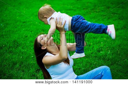 young mother with her baby outdoor on a summer day