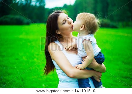 young mother and her baby in the park in summertime