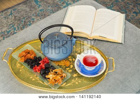 Still Life - Book, cup of tea. dried fruitsa and teapot
