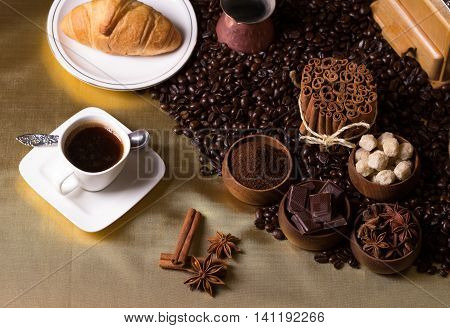 Still-life with coffee, cup with saucer, coffee beans and spices. Coffee time concept