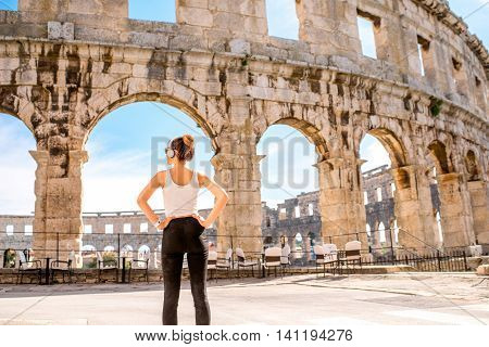 Young sports woman with headphones and smartwatch resting after the training near the ancient coliseum in Pula city. Back view with copy space