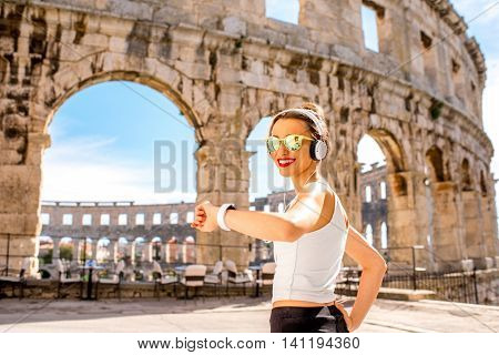 Young sports woman looking at smartwatch standing near the ancient coliseum in Pula city.