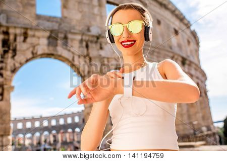 Young sports woman looking at smartwatch during the training near the ancient amphitheatre in Pula city.