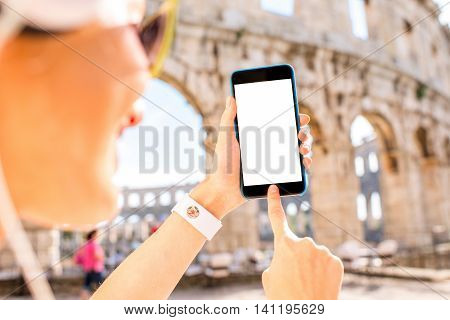 Young sports woman in headphones holding smartphone with white screen on the ancient amphitheatre background