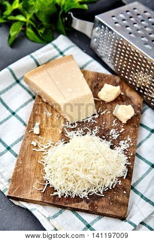 Piece and grated parmigiano reggiano or parmesan cheese on white plate on checkered napkin . Grated parmesan uses in pasta dishes, soups, risottos and grated over salads.