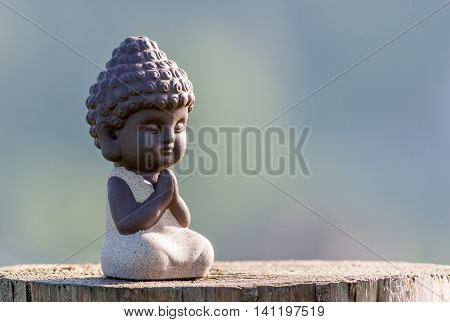 silhouette of little buddha or baby practicing yoga, meditate or pray on wooden surface.