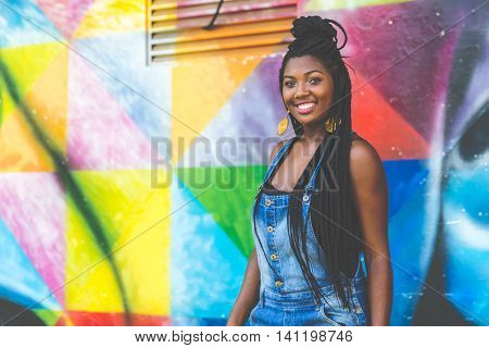 Portrait of Young Afro woman smiling on colorful background