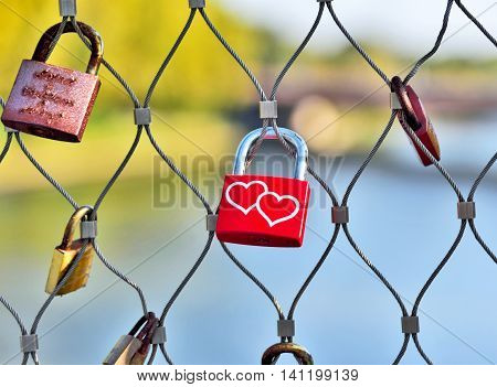 Various padlocks on a fence, focus on a red padlock with hearts, love symbol