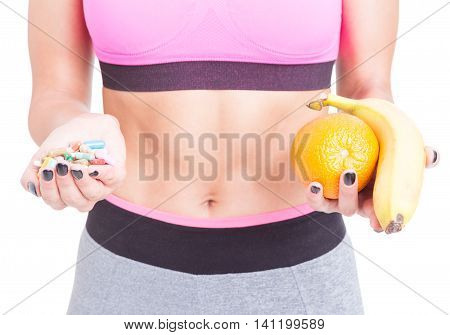 Close-up Of Fit Girl Holding Pills And Fruits
