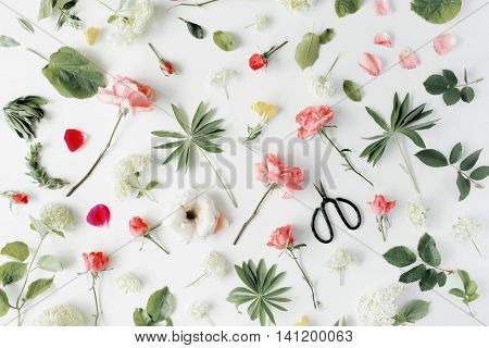 pink roses and scissors on white background. flat lay top view
