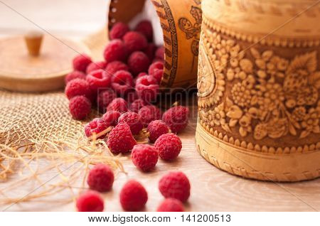 fresh, juicy raspberries scattered on the table from bast banks