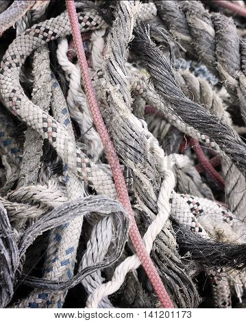 Tangled, old ropes. Stack of old, weathered ropes with selective focus. Close-up of nautical vessel. Chaos scene.