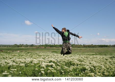 Gracious jump by excited man. Guy flying above flowers field on blue sky background
