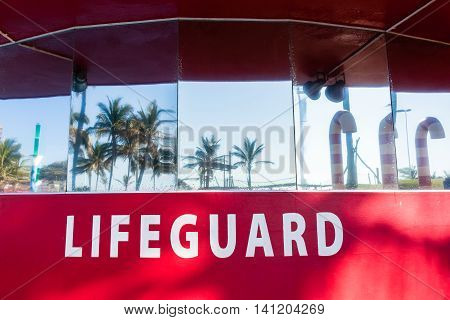 Lifeguard lookout tower office red building on beach ocean pools with reflective glass of trees blue sky.
