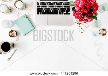 Flat lay top view office table desk. Workspace with laptop red roses bouquet mint diary coffee mug and golden scissors on white background.