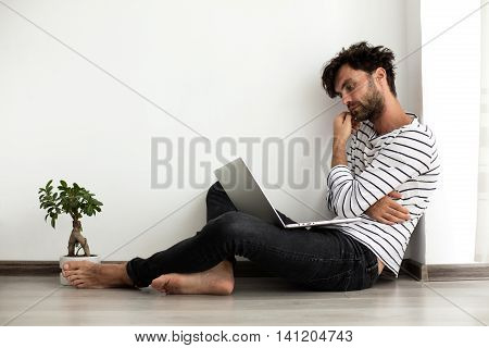 Young Man Sitting Down On The Floor With Laptop And A Plant Next To Him