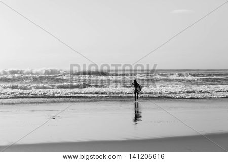 Surfer unidentified beach walks towards ocean waves for surfing session vintage black and white.