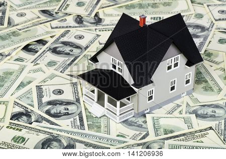 Model of a home on top of hundred dollar bills