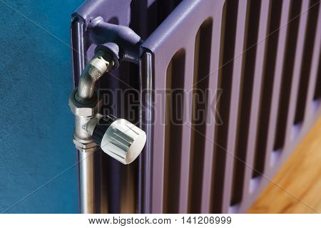 Thermostat on a purple central heating radiator and a blue wall