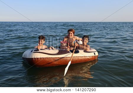 three children with young mom on the dinghy sailing on the sea