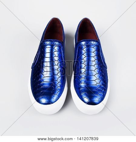 pair of new blue shoes in grey background
