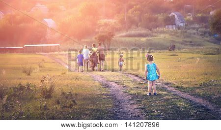 Children go with the pony on the road in a field