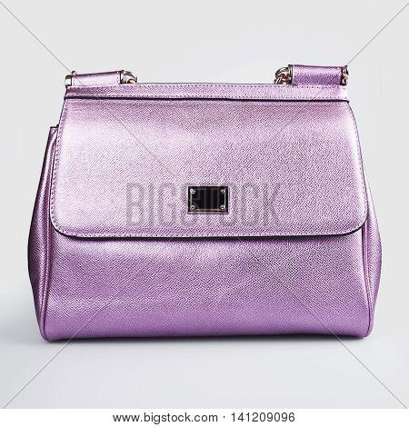 Purple women bag in a grey background