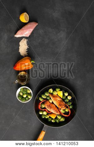 Chicken breasts cooked on the grill pan with Brussels sprouts and sesame on the black chalkboard with raw ingredients