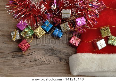 Santa's hat wit shiny gifts and tinsel on a wooden background