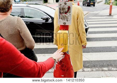 Woman pressing button to cross the street in crowded area in the city of Luxembourg