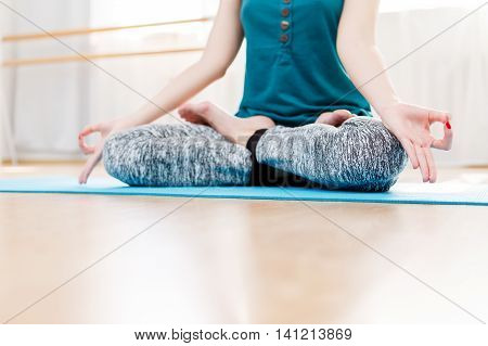Young woman meditating in the gym, in lotus position