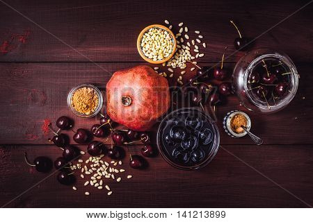 Still life with pomegranate cherry and spices on the red wooden table. Concept of oriental fruits top view