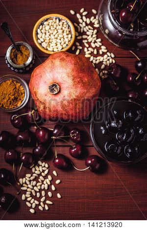 Still life with pomegranate cherry and spices on the red wooden table. Concept of oriental fruits vertical