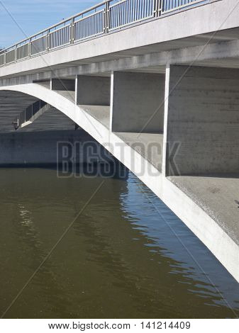 Concrete Bridge Arch Reflected In River Water